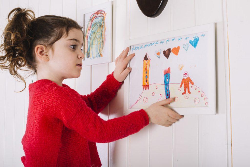 dziewczynka wiesza obraz na ścianie